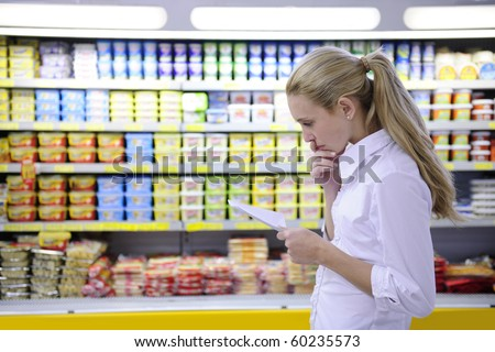 woman reading her shopping list in the supermarket with copy space - stock photo