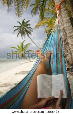 Woman reading in a hammock on a tropical beach - stock photo