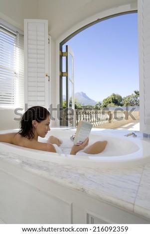 Woman reading in bath by open window, rear view - stock photo