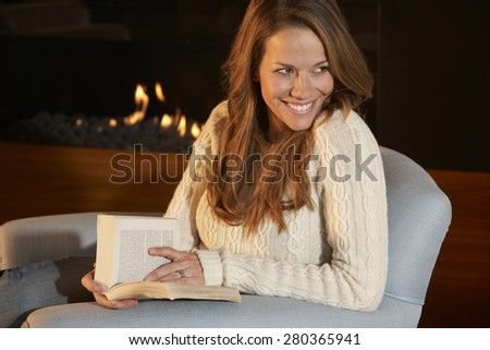 Woman reading in front of fire at home - stock photo