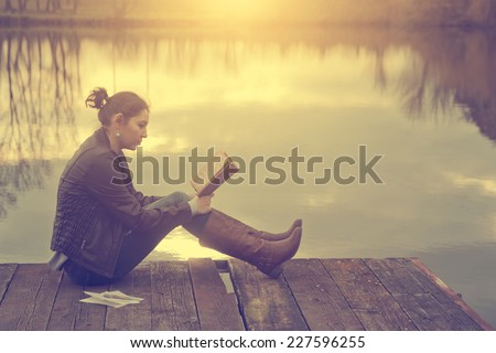 Woman reading in sunset - stock photo