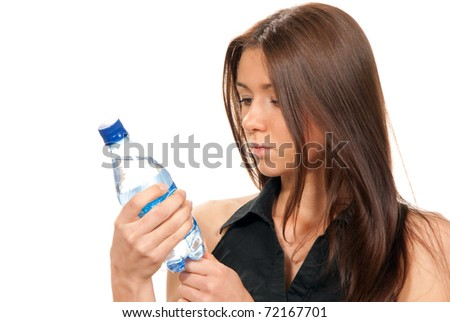 Woman reading lable bottle of pure still drinking water nutrition facts. Female hold in hand sparkling mineral bottled water isolated on a white background. Healthy lifestyle concept - stock photo
