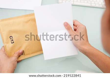 Woman reading letter. Blank card and envelope over grey background - stock photo