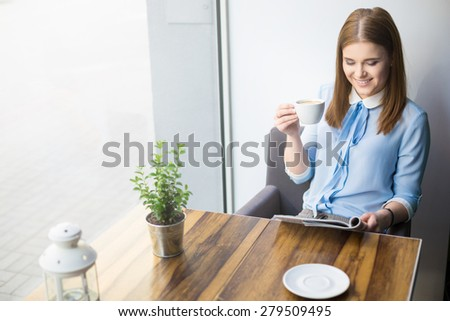 Woman reading magazine and drinking cappuccino in coffee shop - stock photo