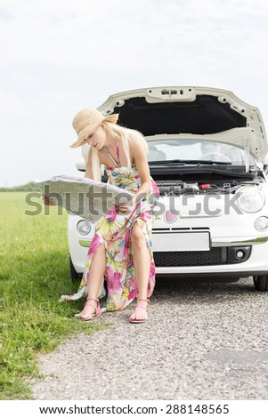 Woman reading map while sitting on broken down car at countryside - stock photo