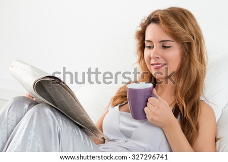 Woman reading morning newspapers sitting at her bed and drinking tea