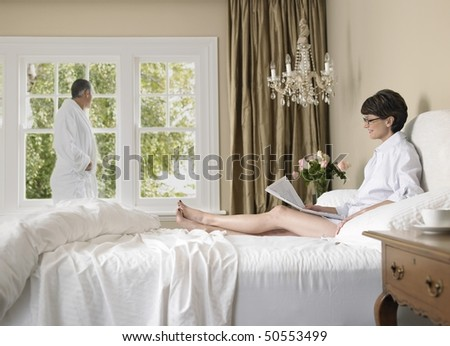 Woman reading newspaper in bed, husband looking through window