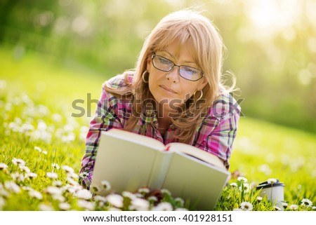 Woman reading outdoors.Happy woman reading a book during springtime in nature. - stock photo