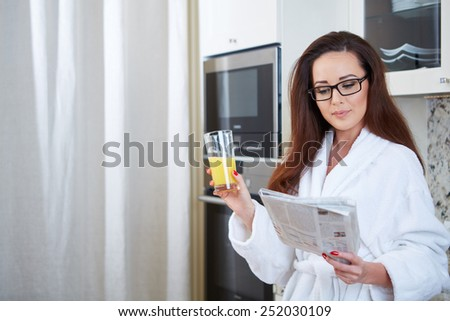 Woman reading the news while drinking orange juice in her kitchen - stock photo
