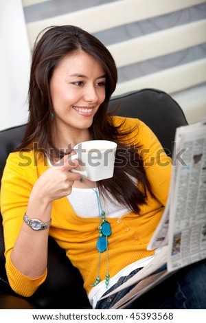Woman reading the newspaper and drinking coffee - stock photo