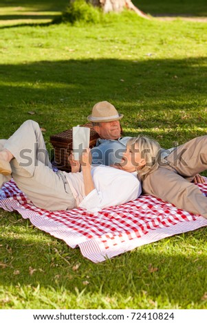 Woman reading while her husband is sleeping in the park - stock photo