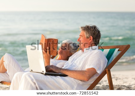 Woman reading while her husband is working on his laptop - stock photo