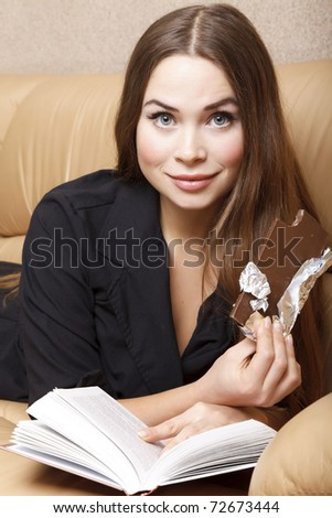 woman reads a book and eating chocolate while laying on the sofa - stock photo