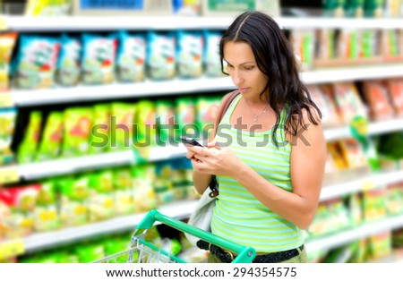 woman reads SMS in supermarket - stock photo