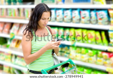 woman reads SMS in supermarkets - stock photo