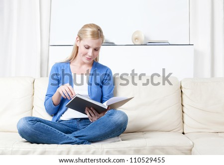 Woman reads the book lying on the white leather sofa - stock photo