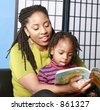 Woman reads to her little boy - stock photo