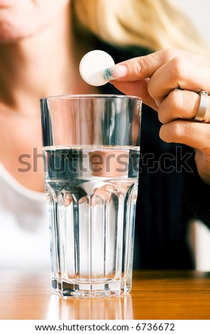 Woman ready to drop a pill into a glass of water (macro)