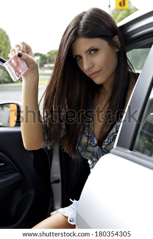Woman ready to pay at gas station - stock photo