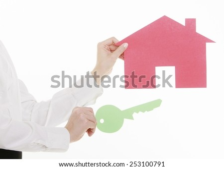Woman real estate agent holding red paper house and key. Property business and accomodation or home buying ownership concept, isolated on white background - stock photo