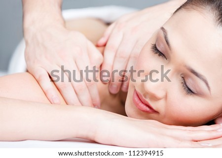 Woman receives body massage at spa salon - stock photo