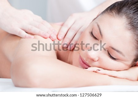 Woman receives body professional massage at spa salon, close up