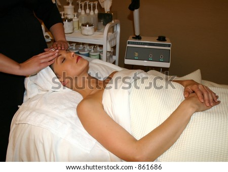 Woman receives facial massage at spa - stock photo