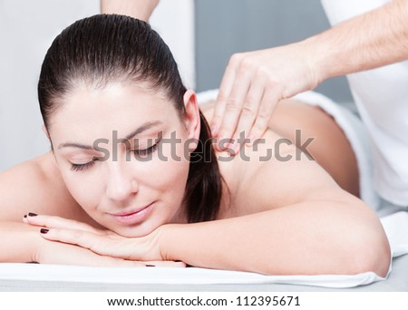 Woman receives massage therapy at spa - stock photo
