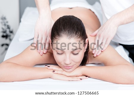 Woman receives relaxing body massage at beauty salon - stock photo