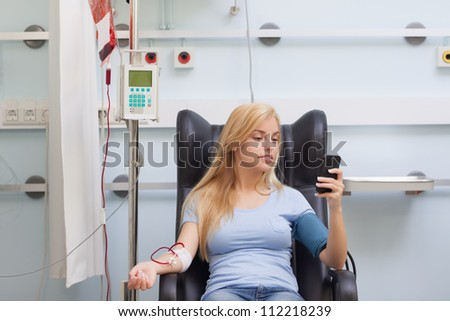 Woman receiving a blood transfusion in hospital ward - stock photo