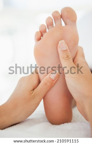 Woman receiving a foot massage at the health spa - stock photo