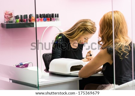 Woman receiving a manicure by a beautician - stock photo