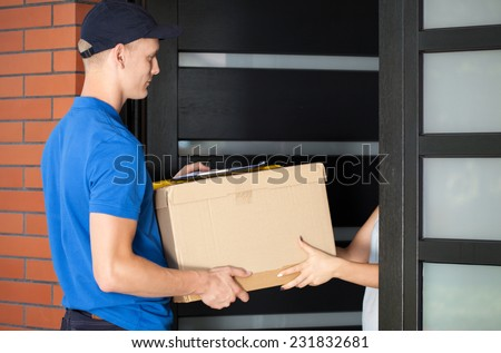 Woman receiving a parcel from a delivery guy - stock photo