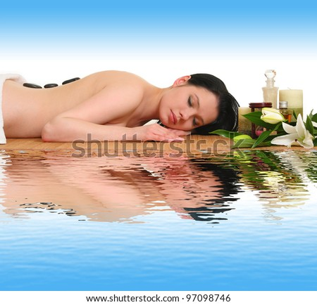woman receiving a therapy with hot stones in spa center