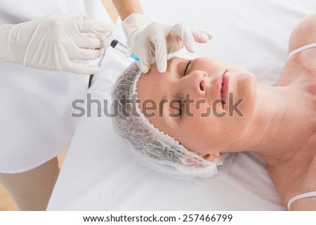 Woman receiving botox injection on her forehead in medical office - stock photo