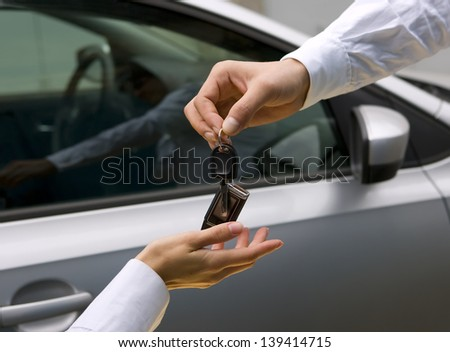 woman receiving car key from man - stock photo