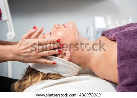 Woman Receiving Facial Massage In Beauty Parlor - stock photo