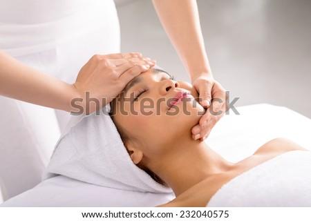 Woman receiving facial massage in spa salon - stock photo