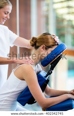 Woman receiving massage in massage chair at spa - stock photo