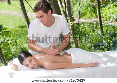 Woman receiving massage outdoors from professional masseuse - stock photo