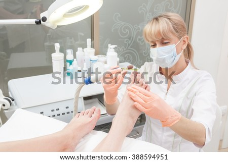 Woman receiving pedicure in a Day Spa, feet nails get cut and polish - stock photo