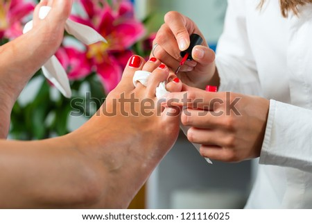 Woman receiving pedicure in a Day Spa, feet nails get polish - stock photo