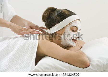 Woman receiving spa facial treatment and massage - stock photo