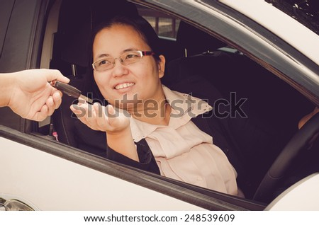 woman receiving the keys of her  car - stock photo