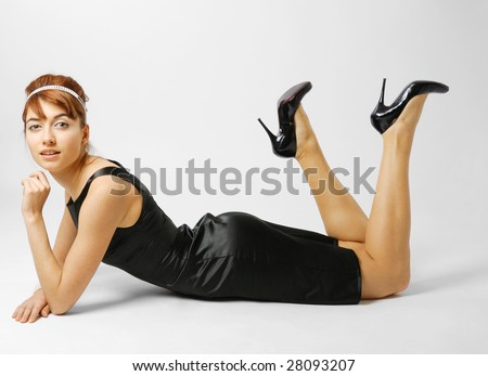 Woman reclining in small black dress, slender legs lifted in heeled shoes