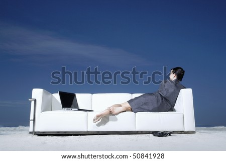 Woman reclining on sofa on beach, back view