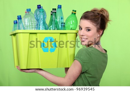 Woman recycling crate of plastic bottles - stock photo