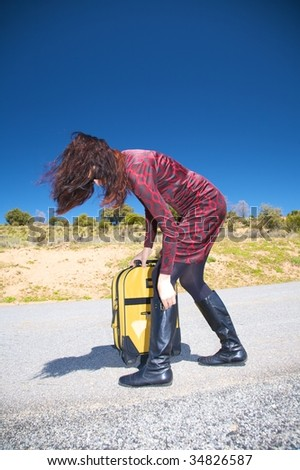 woman red dress with suitcase on the road