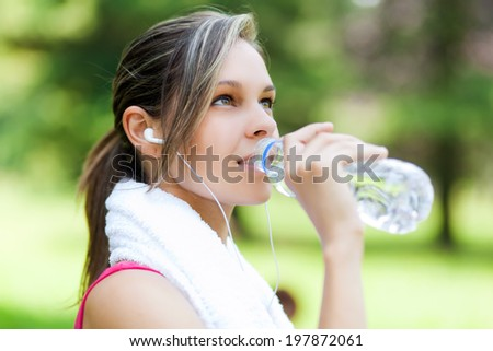 Woman refreshing after running at the city park - stock photo