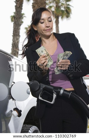 Woman refueling car while counting  money at fuel station - stock photo